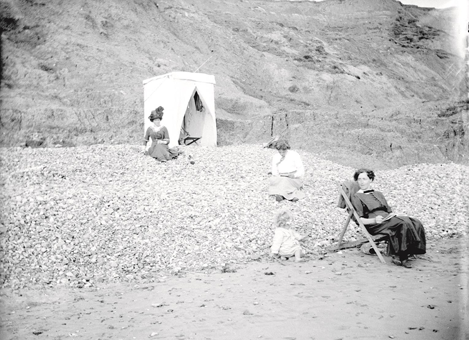 Beach scene at the Isle of Wight in 1913, with Alfred's mother in the background.  The woman with the white blouse is probably his sister Irene Barton/Lock with her daughter Alison born in 1911.  The other sister in the deckchair might be Ethel Grace.  Glass plate negative.